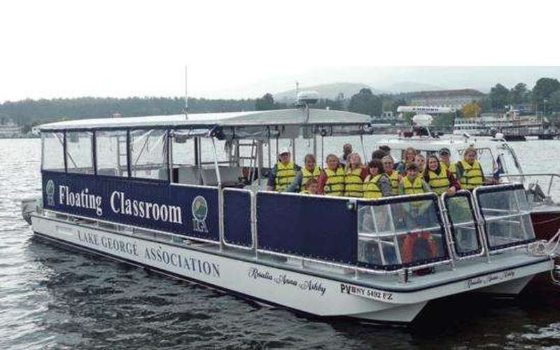The Lake George Association's Floating Classroom with a group of kids in yellow lifejackets aboard