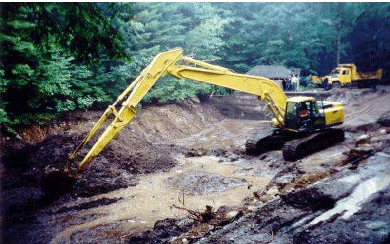A yellow heavy machinery truck digs in a muddy area