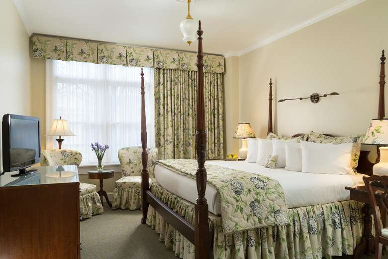 four-poster king-sized bed in a room with long curtains