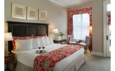king-size bed in a bed and breakfast with white bedding and red/pink accents