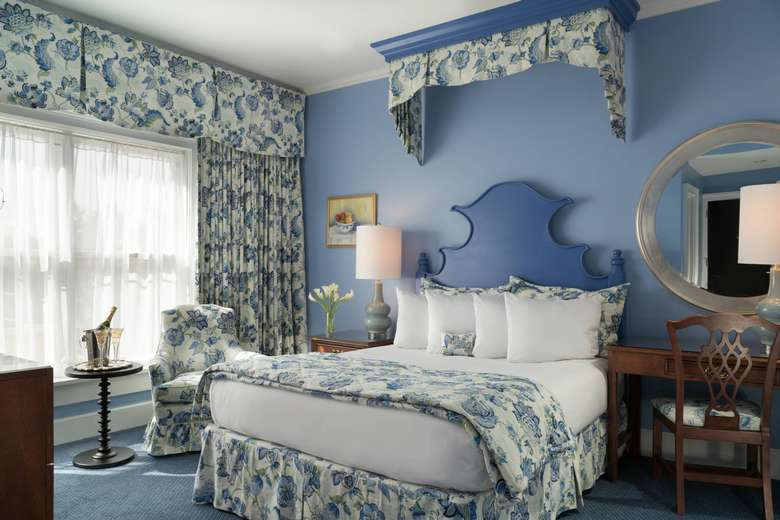 king-size bed in a room with blue walls, accents, and curtains