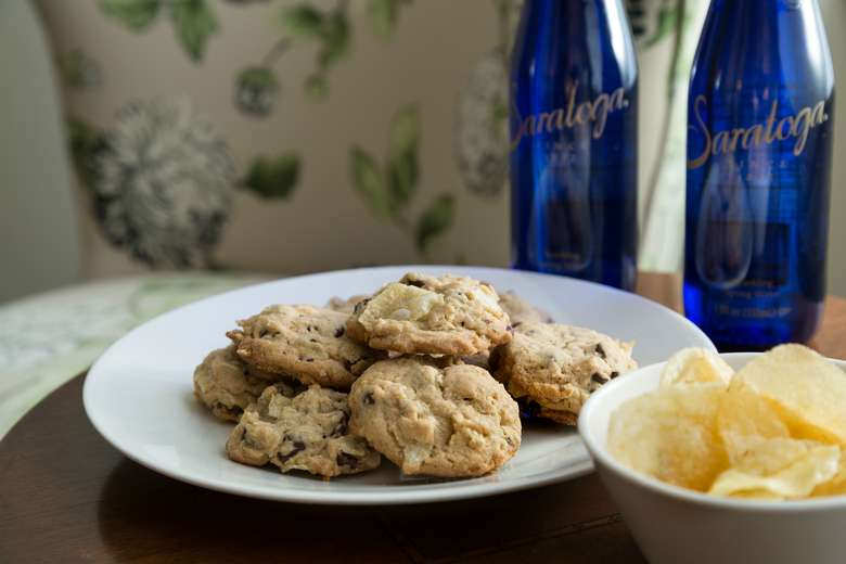 plate of chocolate chip cookies with two blue bottles of saratoga water