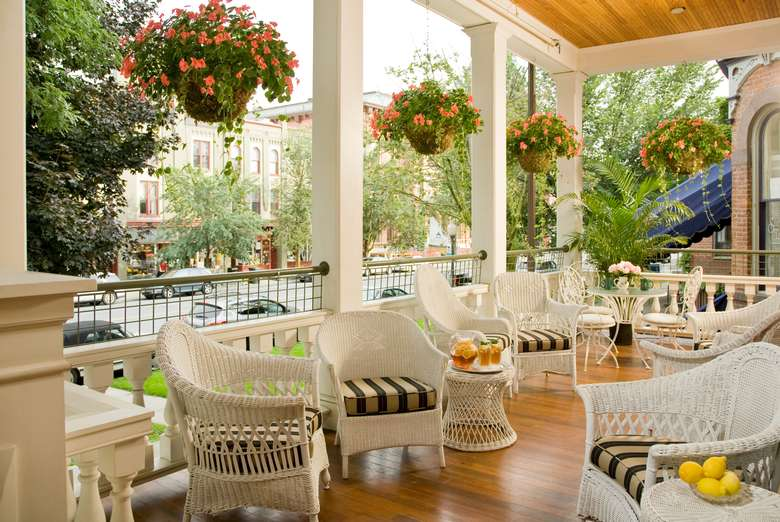 large covered porch with hanging flower baskets and tables and chairs