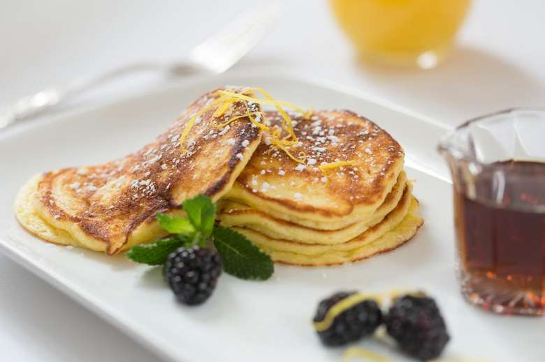 stack of pancakes with blackberries and syrup