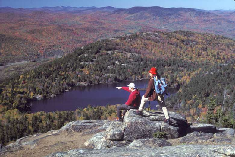two people posing at the summit of crane mountain in the fall