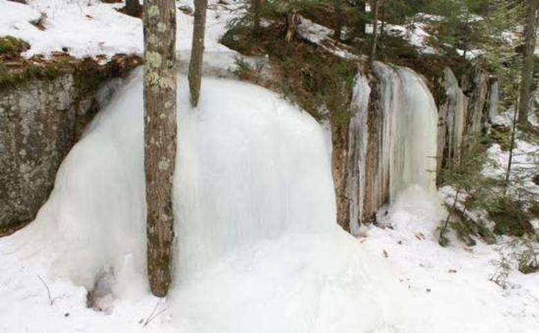 frozen waterfall on the side of a hiking trail