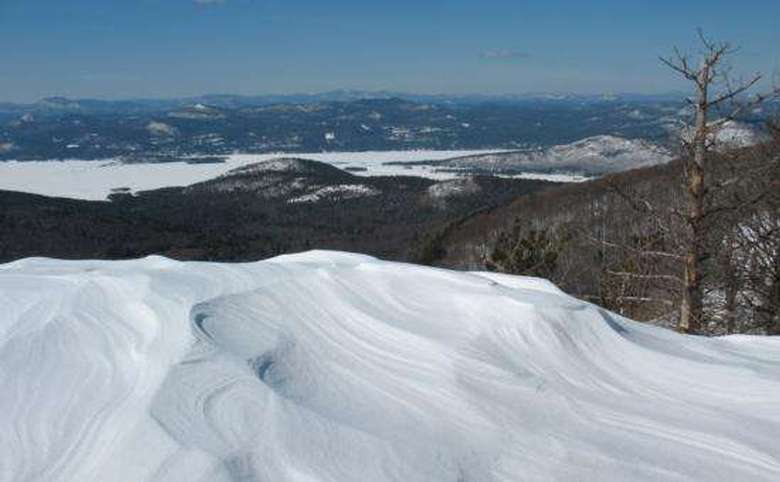 view from the sleeping beauty mountain summit in winter with lake george in the background