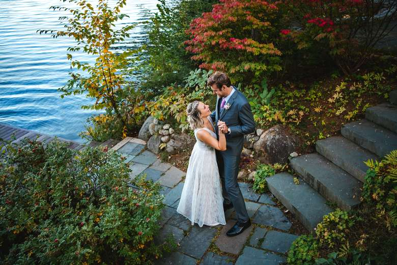 a wedding couple embracing next to the lake
