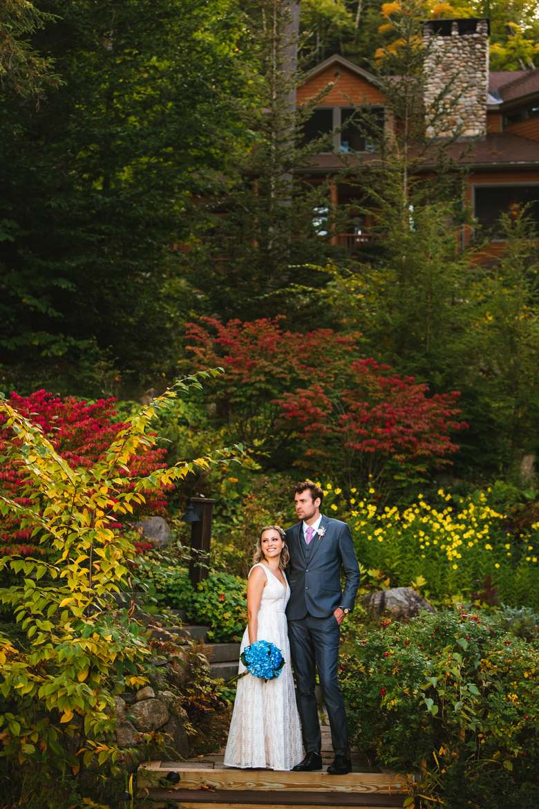 a wedding couple standing in the gardens with beautiful autumn foliage