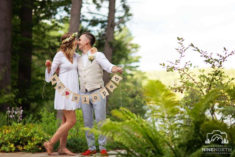 """a wedding couple that just married holding a sign that says """"we eloped!"""""""