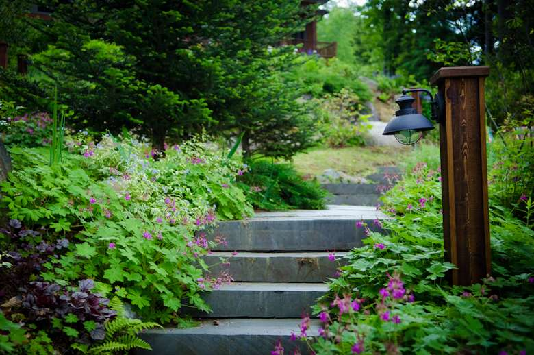 a slate walkway winds down through the gardens to the lake