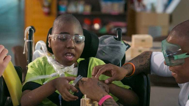 Boy in a wheelchair doing a craft with help from a male counselor