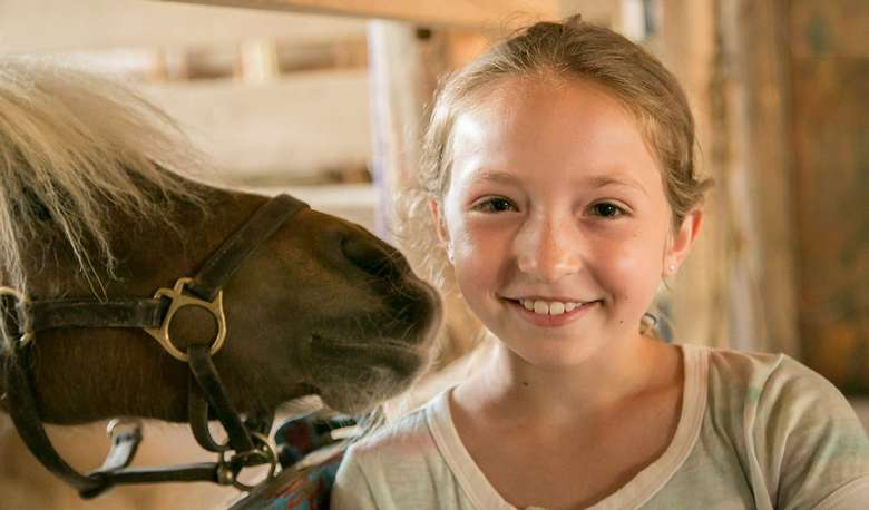 Young girl posing with a horse