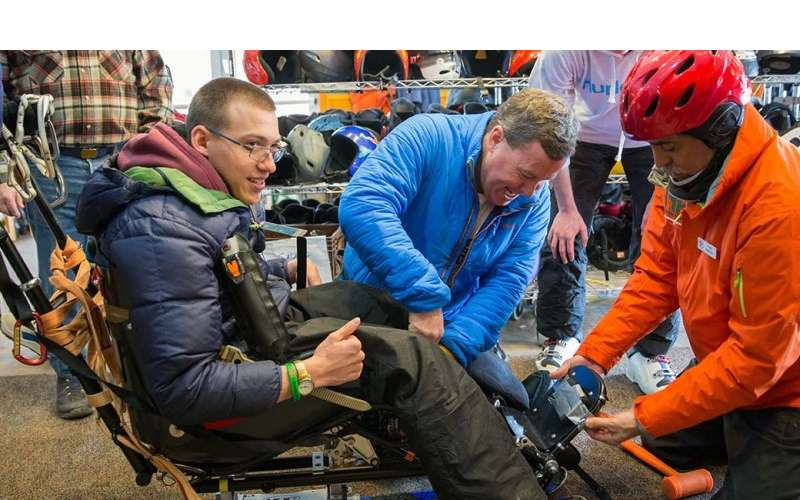 A young man getting fitted for adaptive ski equipment