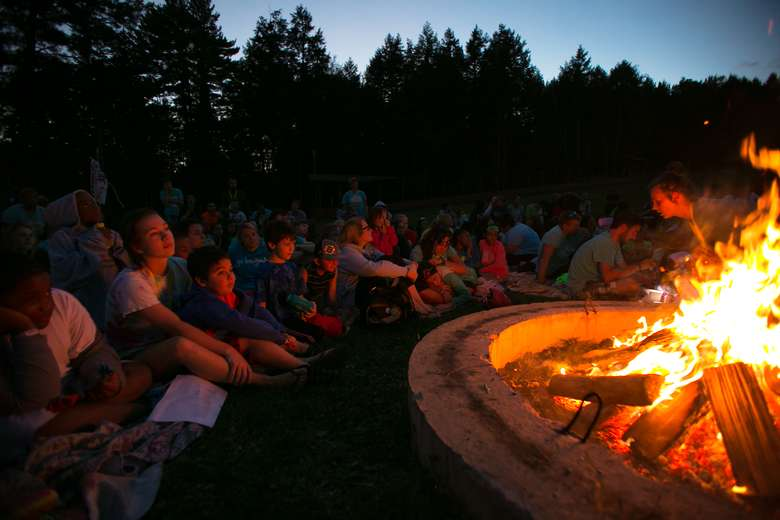 Kids and counselors sitting around a campfire