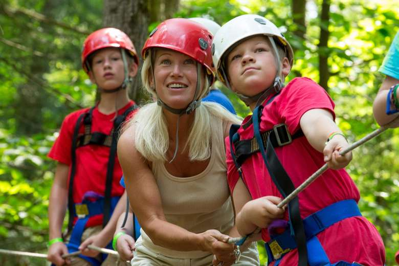 Female counselor in a red helmet helping kids in red and white helmets through a ropes course