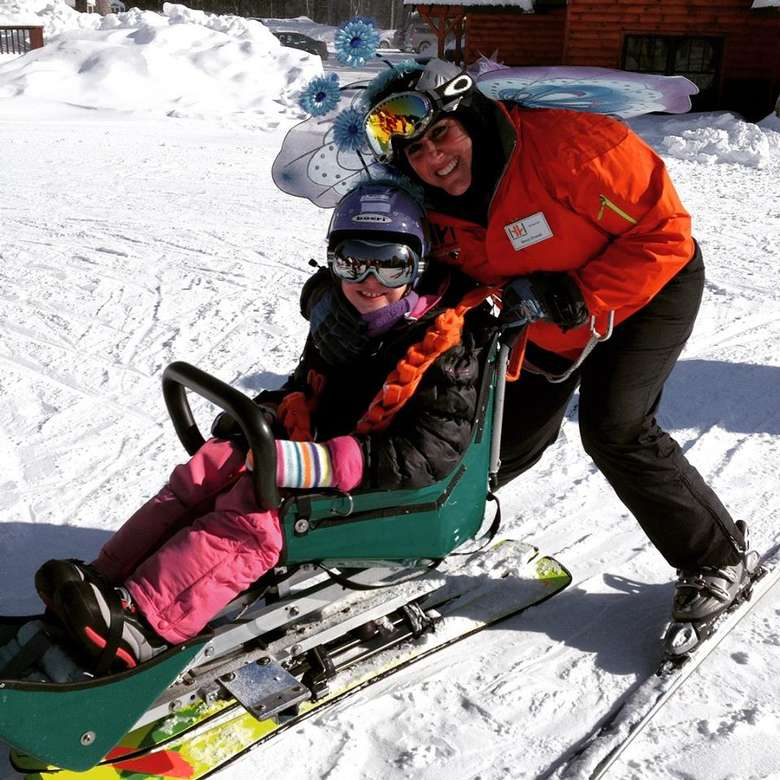 A young girl in a green sled-ski