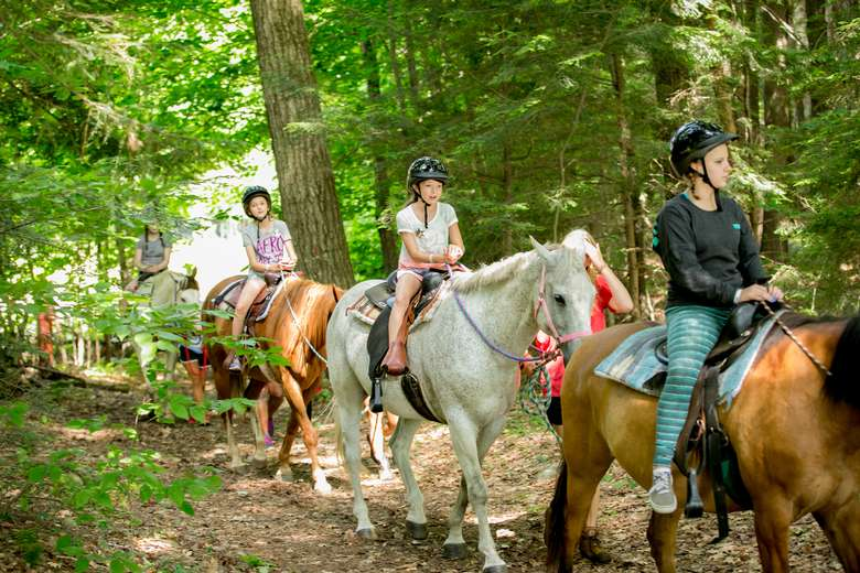 Girls horseback riding through the woods