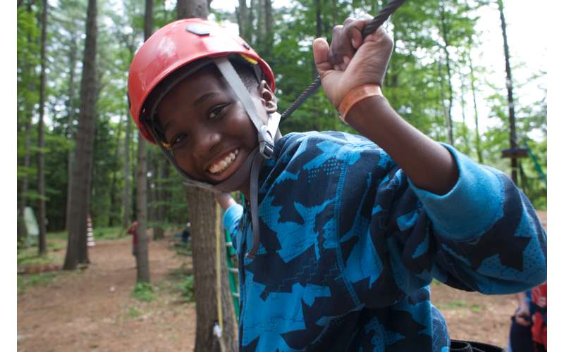 A young boy in a red helmet smiling on a ropes course