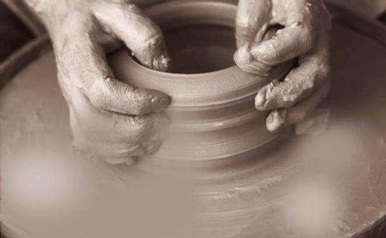 artist working with clay on a wheel