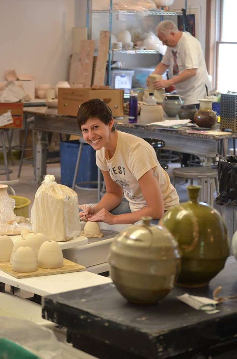 smiling artist working with clay