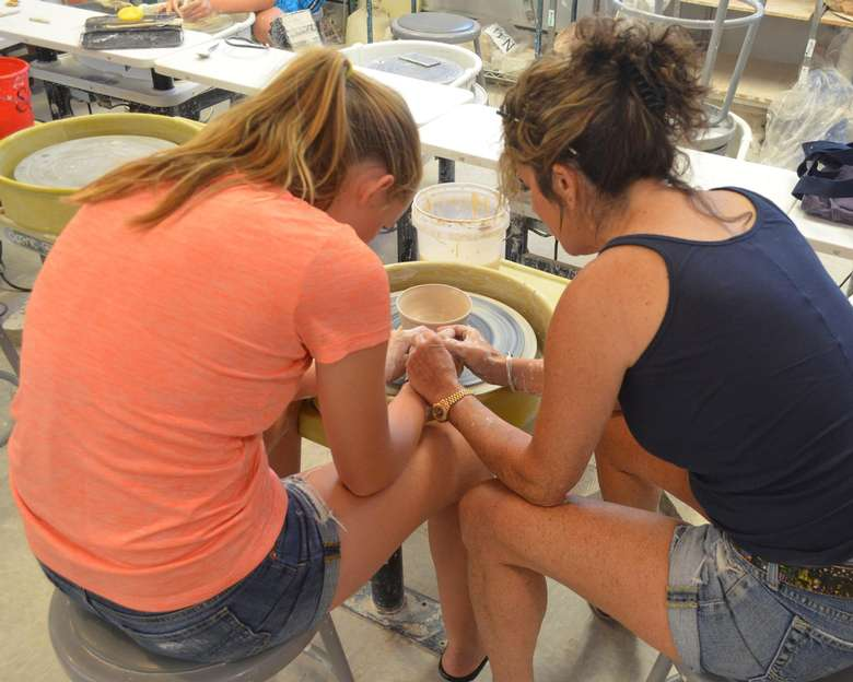 two women working with clay on a wheel