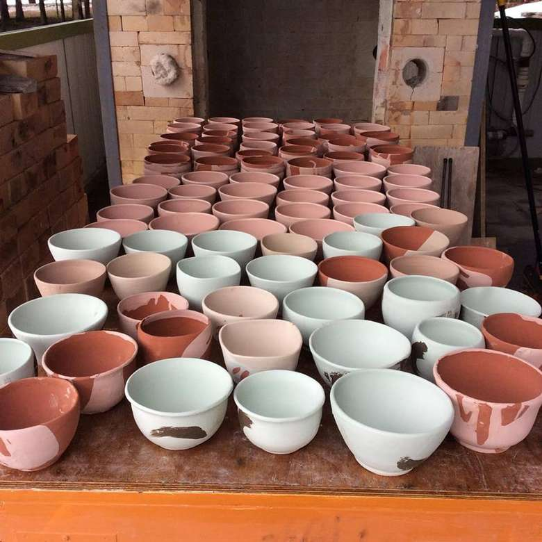 dozens of handmade clay bowls on a table