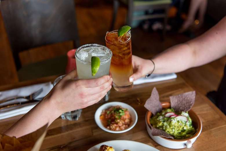 two people raising glasses over bowl of guacamole and chips