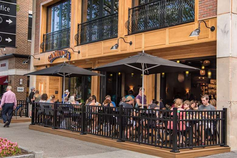 people seated at patio outside restaurant in a city