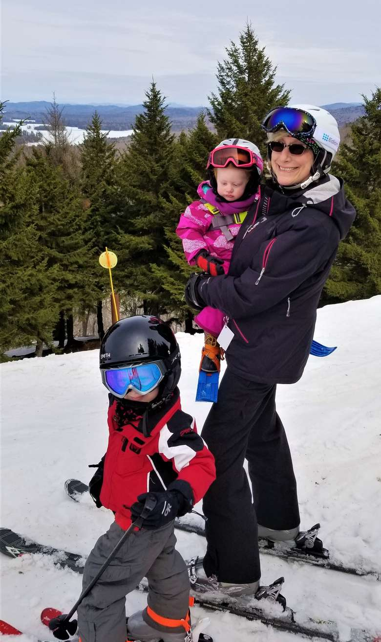 Grandma with her two grandchildren on the top of McCauley Mountain wearing skis