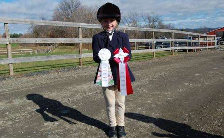 young equestrian participant holding up ribbons
