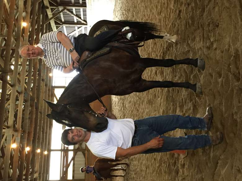 man holding a horse while another man rides it
