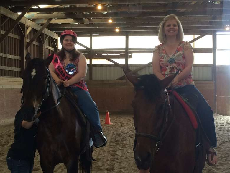 two women on horseback in an indoor facility