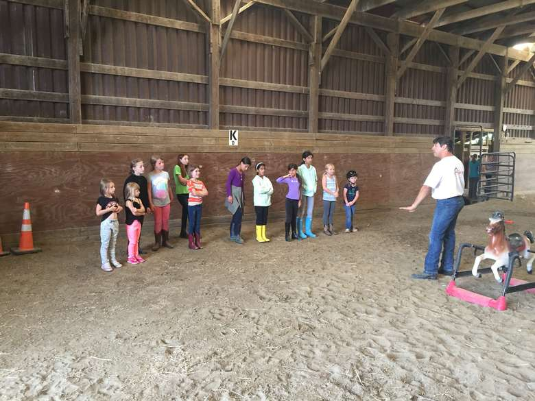 man instructing a group of kids about horses