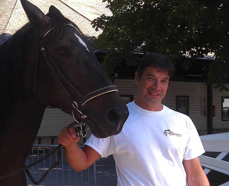man in a white t-shirt leading a dark colored horse