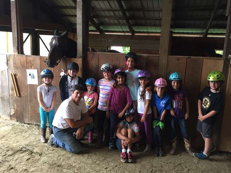 group of kids wearing helmets ready to ride horses at a birthday party