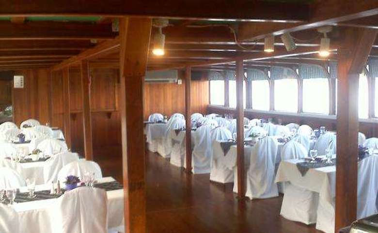 dining room on a boat featuring white tablecloths and chair covers