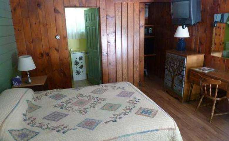 inside of a motel room with a queen size bed and wood paneling on the walls