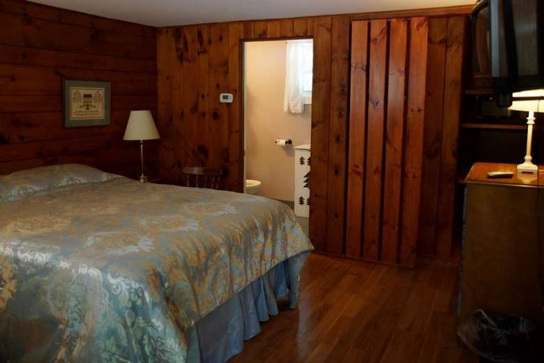 motel room with a queen size bed and wood paneling on the walls