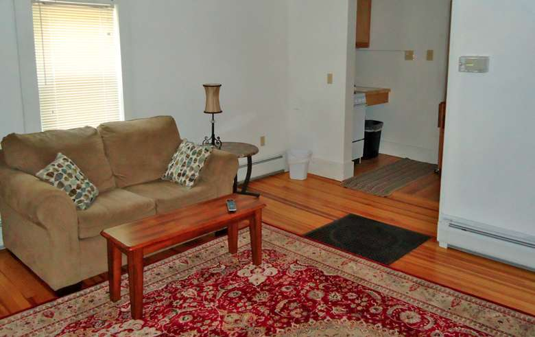 a love seat and coffee table on top of an oriental rug