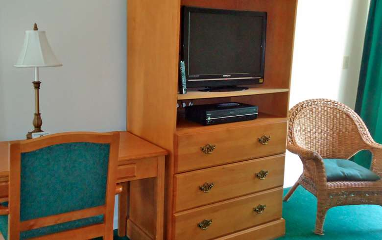 wooden storage unit with a tv and three dresser drawers