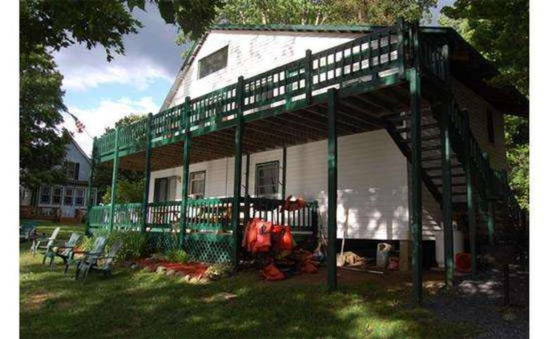 lodge with green wrap around porch and upstairs deck