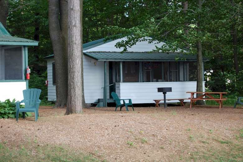 small cottage with picnic table and grill outside