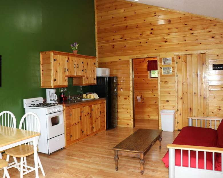 inside a living area with a futon, table, chairs, wood panel walls