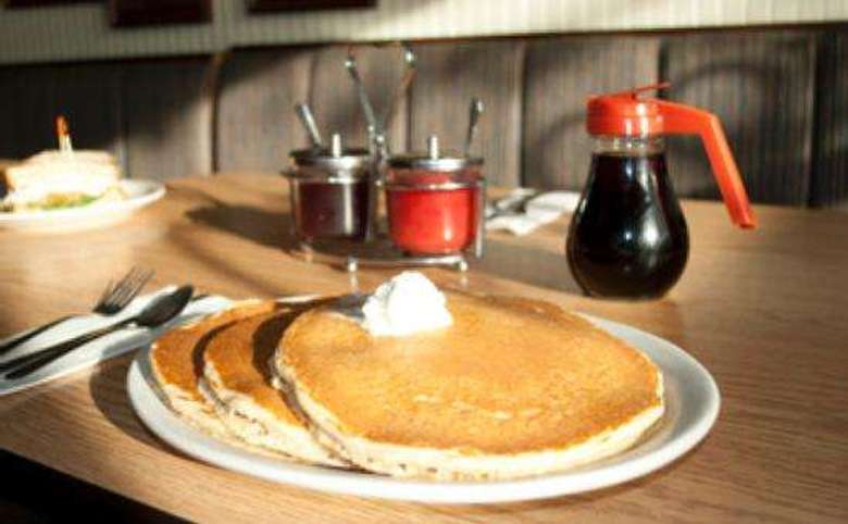 plate of pancakes with a jug of syrup in the background