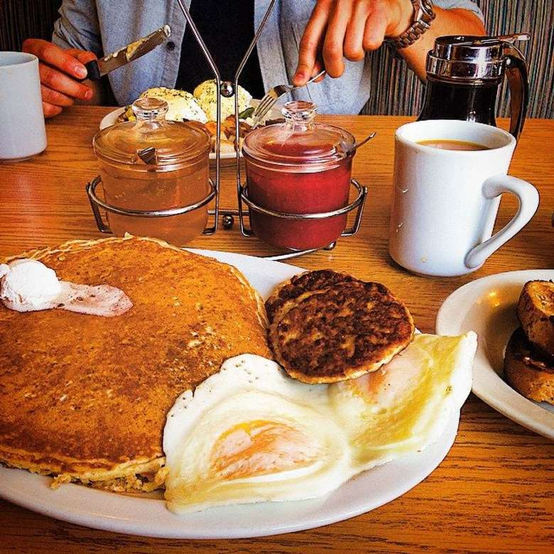 plate with pancakes, eggs, and sausage patties with someone else eating breakfast in the background