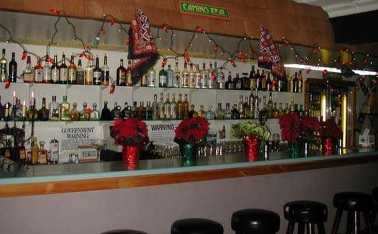 bar in a mexican restaurant with stools in front and lots of bottles of liquor on the shelves behind the bar