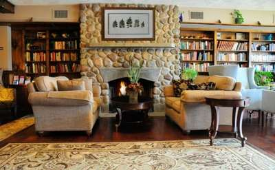 sitting area of the great room with book lined shelves and fire in large stone fireplace