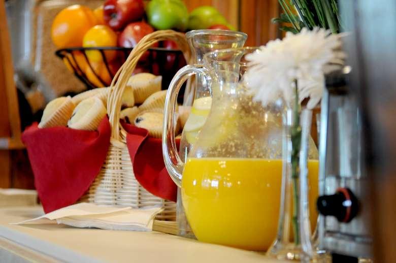 orange juice, muffins, water with lemon, fruit on table