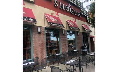 tables outside restaurant with shogun logo on wall